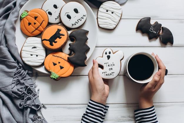 La fille se prépare pour halloween, boire du café et manger des biscuits effrayants.