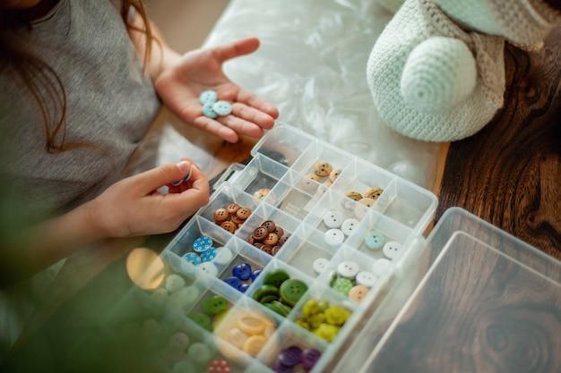 La fille se prépare pour noël et décore des bonhommes de neige tricotés avec des boutons. concept de décoration du nouvel an. les biscuits au pain d'épice sont sur la table. branches de cacao et d'arbres de noël.