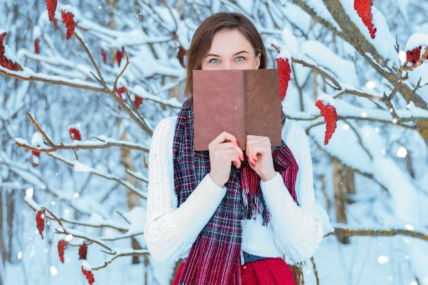 La fille se promène dans la forêt d'hiver