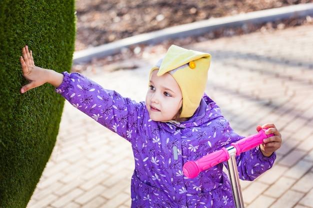 Une fille se promène dans la rue, dans la ville, monte un scooter, une promenade avec sa famille, l'enfance, la joie, le printemps