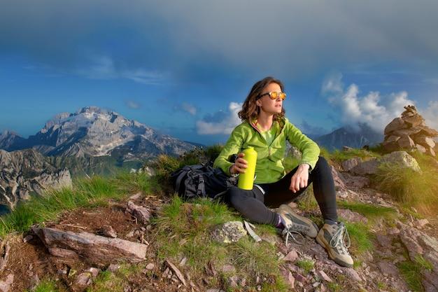 Une fille se repose après avoir gravi le sommet d'une montagne