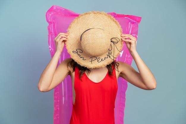 La fille se repose sur un matelas pneumatique rose, elle a couvert son visage d'un chapeau de paille