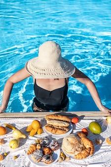 Une fille se tient dans l'eau bleu clair dans la piscine avec un délicieux petit-déjeuner