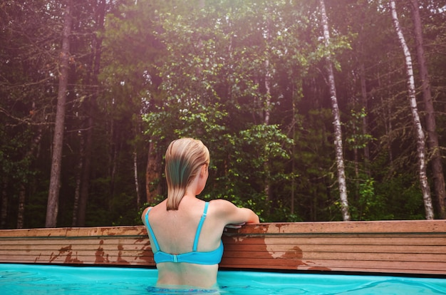 Une fille se tient dos à elle dans la piscine en pleine forêt.