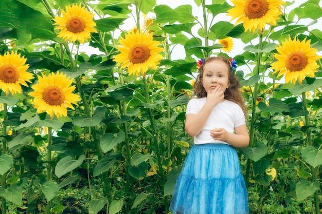 La fille se tient parmi les tournesols