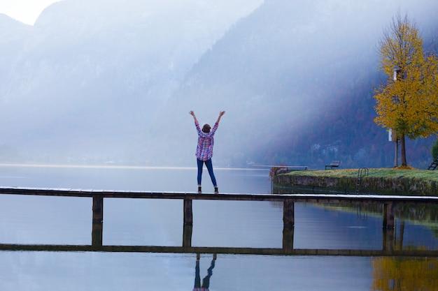 La fille se tient sur un pont en bois sur un lac de montagne tôt le matin. beau paysage et reflet