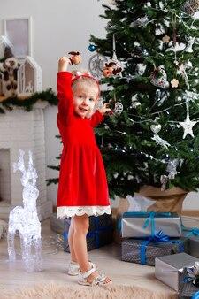 Une fille se tient près de l'arbre de noël avec des cadeaux