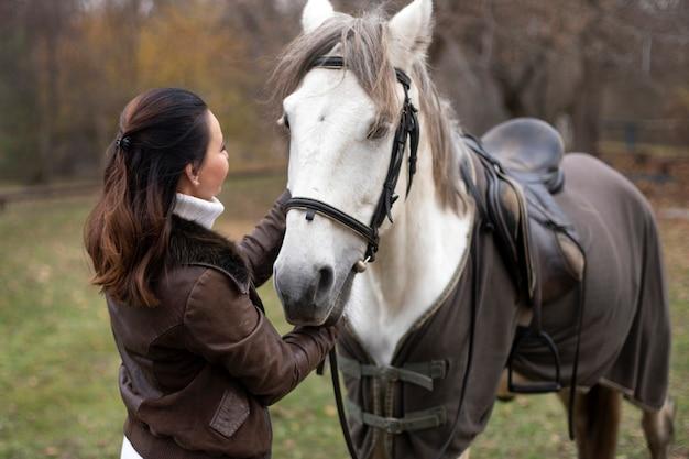 Fille se tient près du cheval blanc