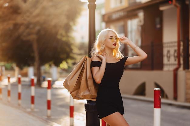 Fille séduisante blonde après le shopping, surcharge de sacs