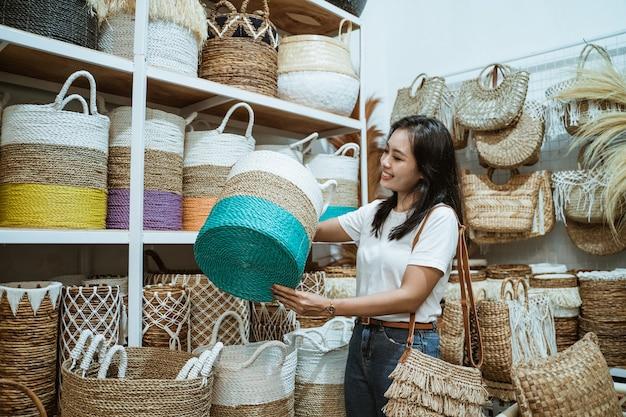 Une fille sélectionne et soulève un panier en osier contre un assortiment d'artisanat en osier dans une boutique d'artisanat