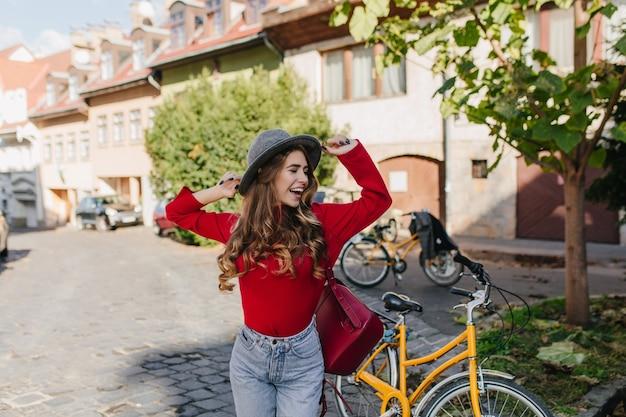 Fille sensuelle aux cheveux longs en pull rouge s'amusant en plein air avec vélo