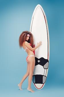 Fille sensuelle tenant une planche de surf
