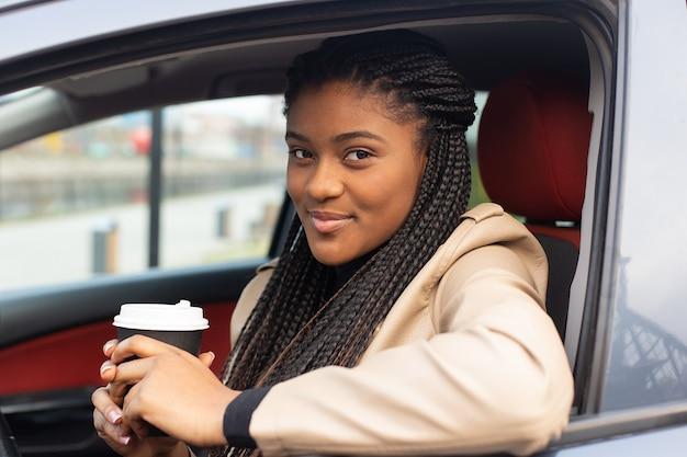 Fille sérieuse au volant d'une voiture, boire du café, afro-américain