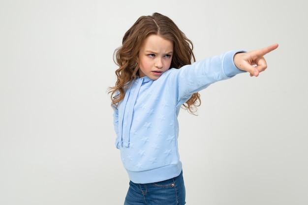 Fille sérieuse en capuche bleu décontracté pointe un doigt sur le côté sur un mur de studio gris clair
