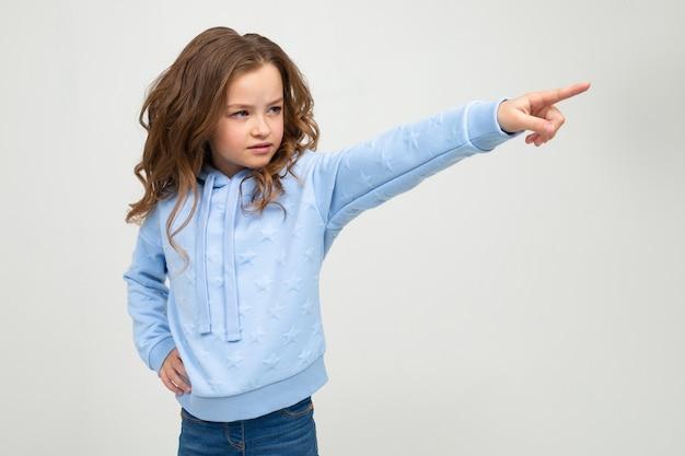 Fille sérieuse en capuche bleu décontracté pointe un doigt sur le côté sur un mur de studio lumineux