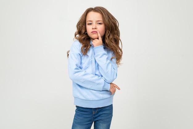 Fille sérieuse dans un chandail à capuchon bleu décontracté se dresse avec une expression honnête sur un mur blanc avec un espace vide