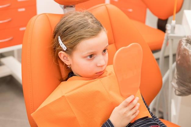 Fille sérieuse regardant miroir dans la chaise des dentistes