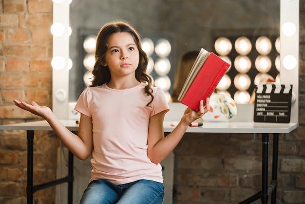 Fille sérieuse tenant un livre rouge dans sa main en haussant les épaules