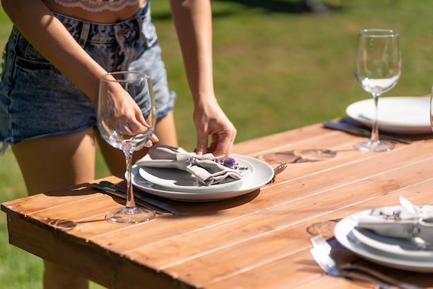 Fille le serveur dans un café d'été à ciel ouvert met la vaisselle sur une table en bois.