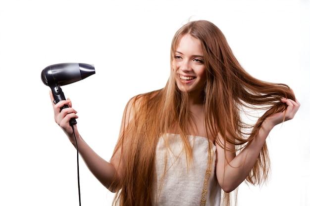 Fille en serviette blanche séchant les cheveux avec sèche-cheveux