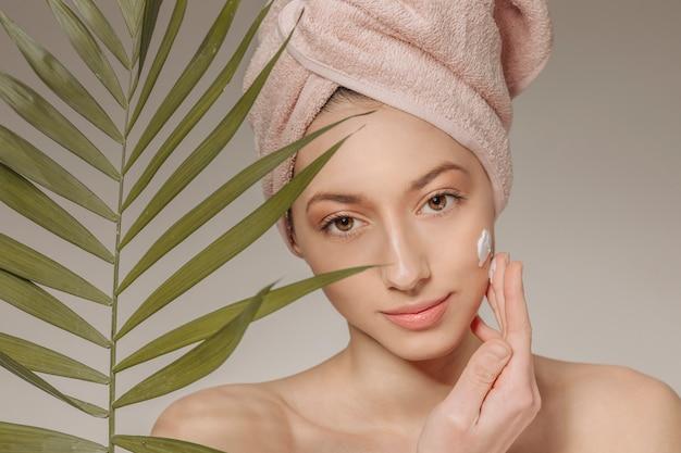 Fille avec une serviette sur la tête avec une feuille
