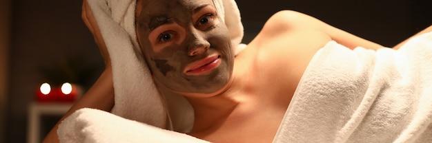 Fille avec une serviette sur la tête et masque de boue son portrait de visage