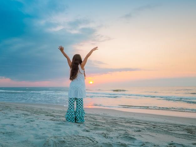 Fille avec ses mains levées haut debout sur la plage entourée par la mer pendant le coucher du soleil