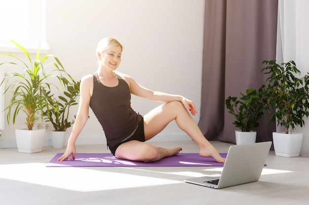 Fille seule faisant des exercices de yoga en ligne sur un ordinateur portable sur le sol dans la salle lumineuse, restez à la maison en toute sécurité.