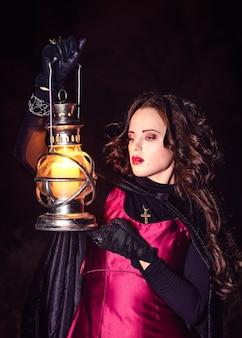 Une fille seule la nuit dans la forêt prépare une potion et des merveilles pour le mariage, entourée de bougies et de fumée