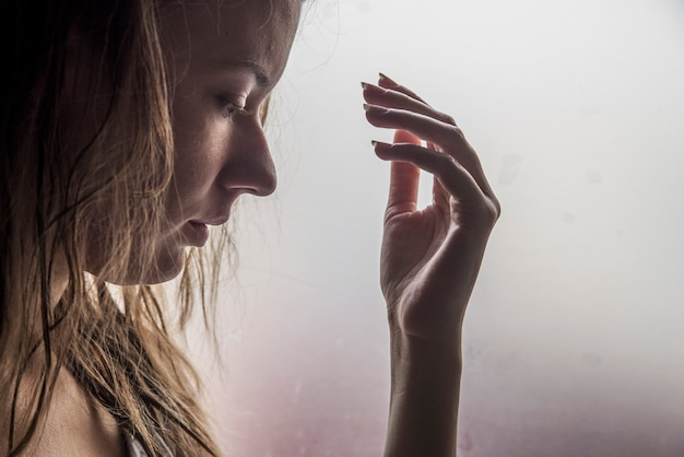 Fille seule près de la fenêtre en train de penser à quelque chose. triste femme regarde la pluie tomber dans une fenêtre à la maison