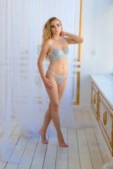 Fille sexy aux cheveux blonds ondulés en lingerie allongée sur le lit et posant dans un intérieur ancien vintage