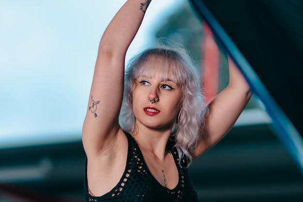 Fille sexy blonde avec des tatouages et des piercings, réparation de voiture à l'aide d'outils