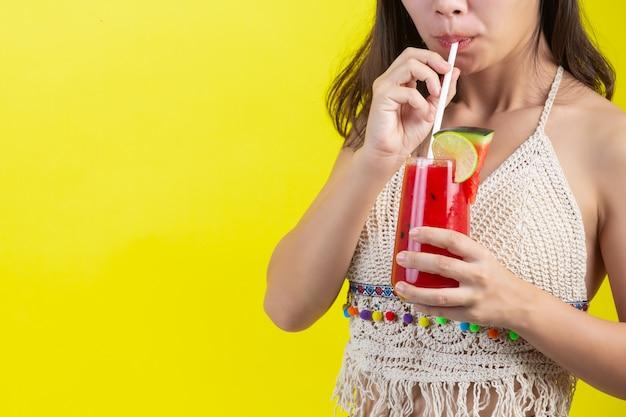 Fille sexy boit de l'eau de melon d'eau par temps chaud d'été avec un chapeau sur le mur jaune.