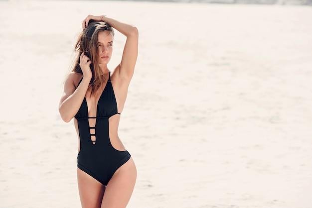 Fille sexy avec un corps sportif parfait en maillot de bain noir relaxant à la plage.