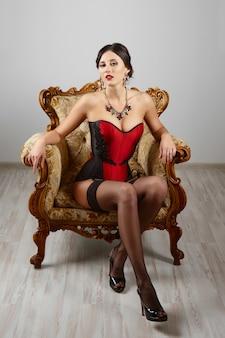 Fille sexy en corset burlesque et lingerie posant contre le mur