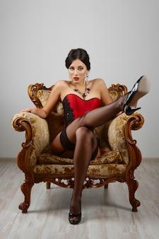 Fille sexy en corset rouge et lingerie posant sur un fauteuil vintage.
