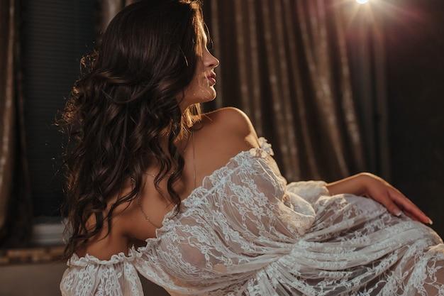Fille sexy dans une tunique transparente sur les sous-vêtements de lit sur un corps gracieux dans la veilleuse d'un