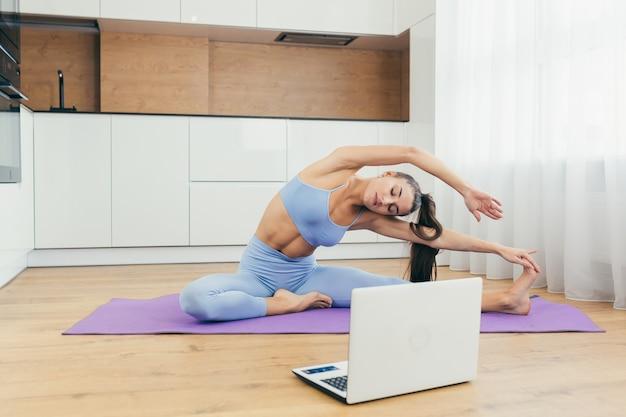 Fille sexy faisant du fitness à la maison en ligne