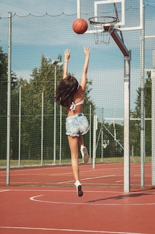 Fille sexy jouant au basket