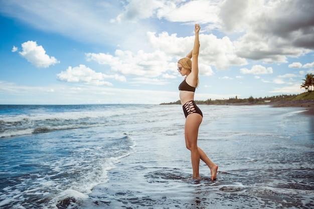Fille sexy en maillot de bain se promène sur la plage noire