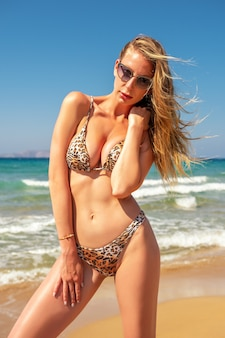 Fille sexy mince avec une silhouette parfaite dans un bikini léopard sur la plage.
