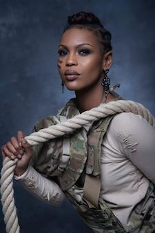 Fille sexy portant un gilet de style militaire posant avec une corde et regardant dans la caméra en studio