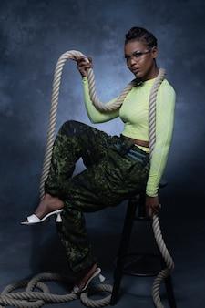 Fille sexy portant un pantalon de style militaire et des sous-vêtements néon posant avec une corde et regardant dans la caméra en studio