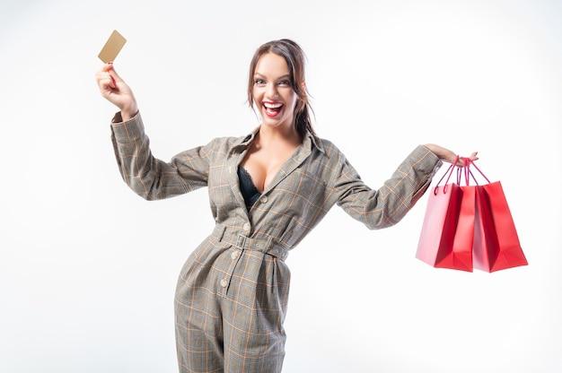 Fille sexy posant avec une carte de réduction et des sacs rouges