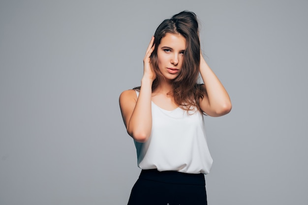 Fille sexy en robe moderne de mode pose en studio sur fond blanc