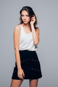 Fille sexy en robe moderne de mode pose en studio isolé sur fond blanc
