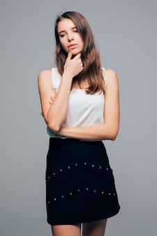 Fille sexy en robe moderne de mode pose en studio tient le bras sur son menton isolé sur fond blanc
