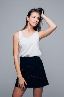 Fille sexy en robe moderne de la mode pose en studio tient ses bras sur les cheveux isolés sur fond blanc