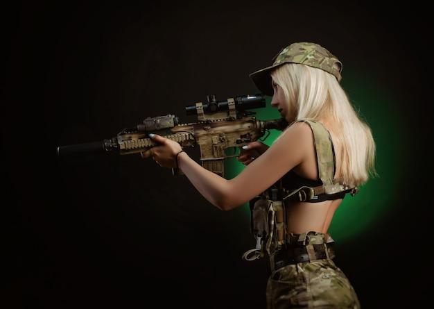 Une fille sexy en salopette militaire d'airsoft pose avec une arme à feu dans ses mains sur un fond sombre