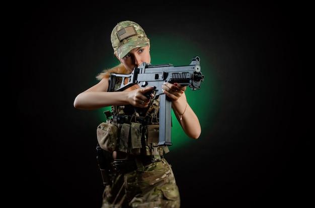 Une fille sexy en salopette militaire d'airsoft pose avec un fusil d'assaut sur un fond sombre